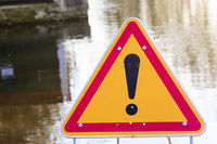warning sign of danger in front of a flooded road