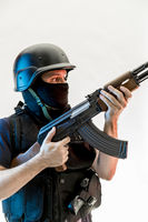 man armed with balaclava and bulletproof vest, gun and shotgun, kalashnikov