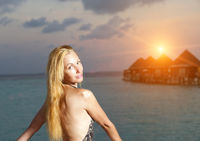 The young woman in a bathing suit at sunset on  background of the sea and silhouettes of houses over water