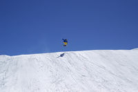 Snowboarder jumping in terrain park on sun winter day
