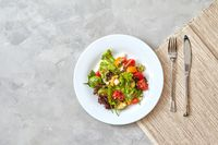 Fresh vegetable salad in a plate with a fork and knife on a gray background,