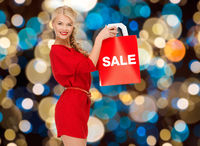 woman in red dress with word sale on shopping bag