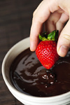 Hand dipping strawberry in chocolate