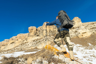 Backpacker with a large backpack and sticks ascends to the rock against the background of epic rocks in the winter season.