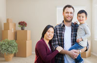 Mixed Race Chinese and Caucasian Parents and Child Inside Empty Room with Moving Boxes.