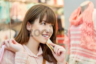 Frau mit Kundenkarte überlegt einen Kauf