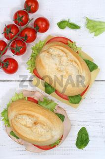 Brötchen Sandwich Baguette belegt mit Käse und Schinken Hochformat von oben auf Holzbrett