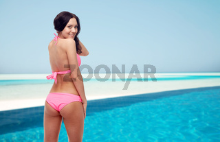 happy young woman in pink bikini swimsuit on beach