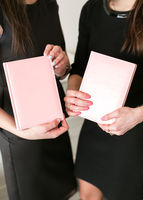 Two girls hold business notebooks in hand. Envelopes in hands close up.