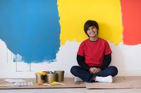 young boy painter resting after painting the wall