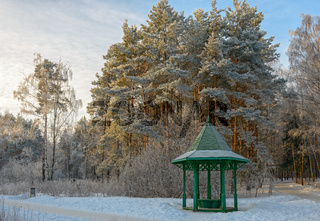 Wooden arbour covered with hoarfrost in winter garden