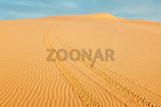 All-terrain vehicle ATV tracks in white sand dunes on sunrise,