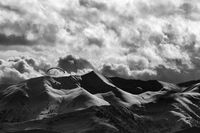 Evening sunlight mountain with clouds and silhouette of paraglider