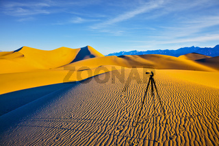 Tripod with camera stands on a sand dune