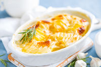 Baked potato gratin with garlic, cream and cheese, traditional french cuisine. White background