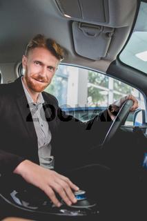 Handsome man sitting inside electro car.