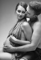 Young man and pregnant woman in studio