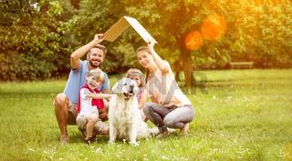 Familie mit Dach über Kopf als Symbol für Hausbau