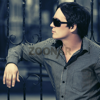 Young handsome man leaning on cast iron fence