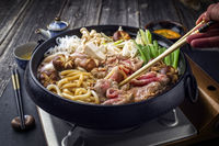 Cooking traditional Sukiyaki pot with Kobe Beef and Vegetable as close-up on slate