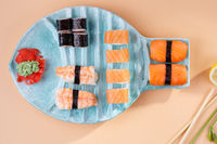 rolls and sushi on a plate in the form of fish