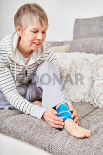 Ältere Frau kühlt Knöchel mit Kompresse