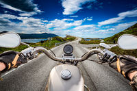Biker rides a road with Atlantic Ocean Road in Norway. First-person view.