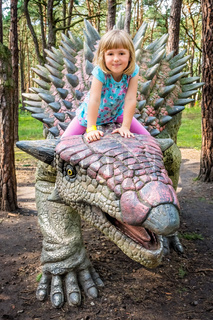 Cute little caucasian girl riding on Ankylosaurus dinosaur