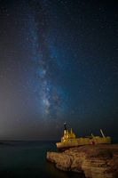 Milky Way and cargoship aground near sea shore