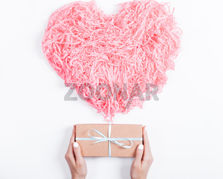 Female hands are holding a box with a gift near the decorative hearts on white background