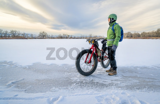 senior cyclist is riding a fat bike in winter