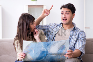 Young family discussing travel plans with map