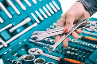 Woman holding a tool for repair on a background of a tool kit