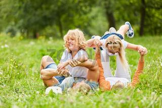 Kinder toben mit ihren Eltern im Gras herum