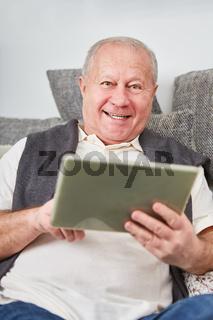 Älterer Mann mit Tablet freut sich