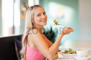 happy young woman eating lunch at restaurant