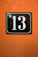 the number thirteen on an orange wall