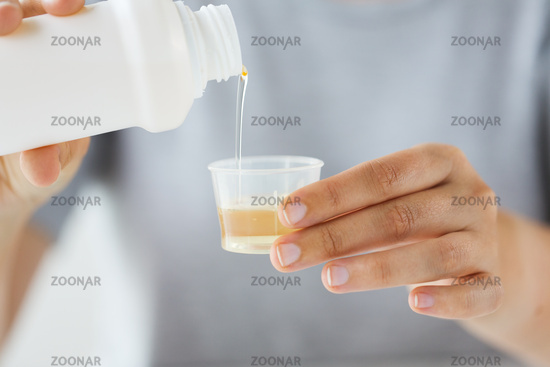 woman pouring syrup from bottle to medicine cup