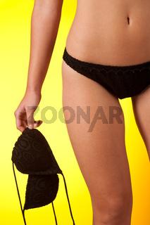 Part of female body wearing black bikini   holding bra