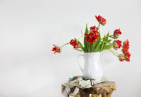 Tulips bouquet in white vase on wooden rustic chair