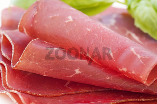 Pressed meat slices rolled as closeup on a white plate