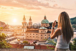 Tourist taking a photo with mobile of beatiful sunset in Salzburg Austria