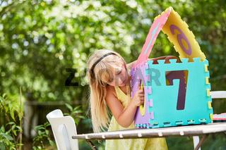 Mädchen baut ein Miniatur Puzzle Haus