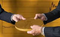 Three traders hands holding large gold coin