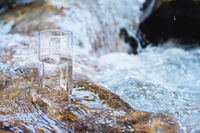 A glass glass with pure mountain drinking water stands on a rock in the course of a mountain river against the backdrop of seething cascades and waterfalls of a mountain river. The concept of pure mineral drinking water. Eco-friendly products healthy conc