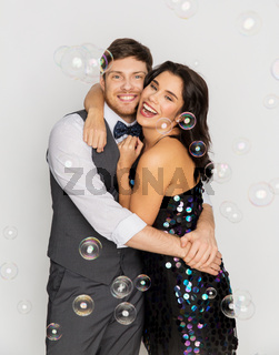 happy couple hugging in soap bubbles at party