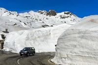 PKW fährt auf der Passtrasse zwischen hohen Schneemauern über den Gotthardpass. Schweiz