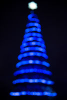 Defocused christmas tree silhouette with blue lights