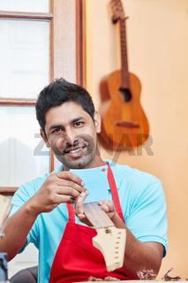 Gitarrenbauer prüft ein Gitarren Griffbrett