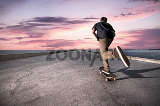Skateboarder pushing on a concrete pavement